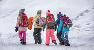 Kinder mit Schulranzen im Schnee