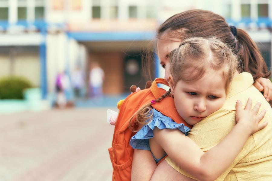 Mädchen umarmt sorgenvoll die Mutter - Angst vor der Einschulung