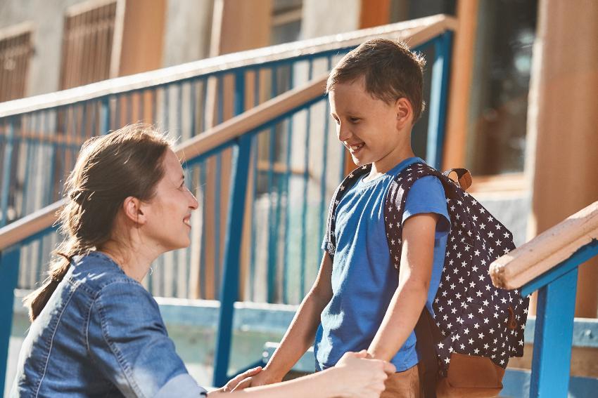 Mutter begleitet Jungen zur Schule, beide sind fröhlich - Angst vor der Einschulung im Vorfeld ausräumen