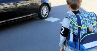 Junge mit Schulranzen mit Reflektorstreifen