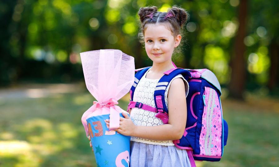 Erstklässlerin mit Schultüte und ergonomischem Schulranzen