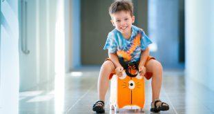 Junge sitzt auf Kinderkoffer - Happy Sammies